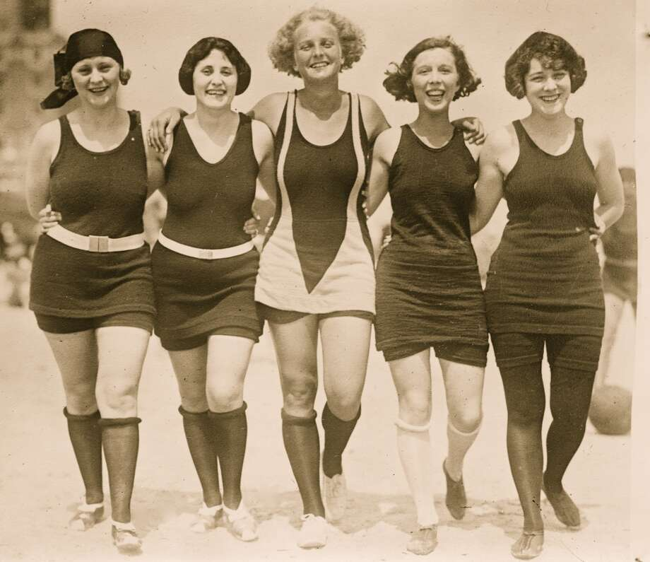 Five unidentified women dressed in bathing suits walk arm in arm on a sandy beach, early twentieth century. Photo: Buyenlarge, Getty Images