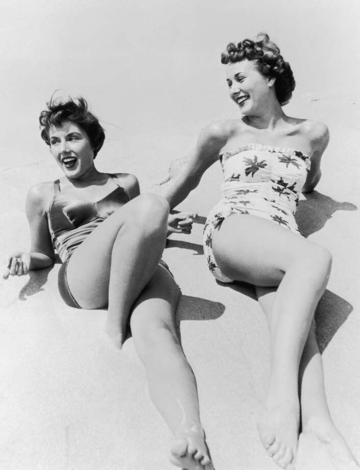 Two women in swimming costumes relax on the beach, circa 1935. Photo: FPG, Getty Images