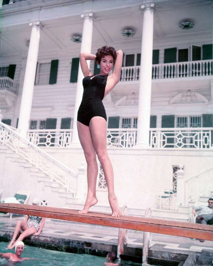 Rita Moreno, Puerto Rican singer, dancer and actress, wearing a black swimsuit, posing on a diving board with swimmers below, circa 1955. Photo: Silver Screen Collection, Getty Images