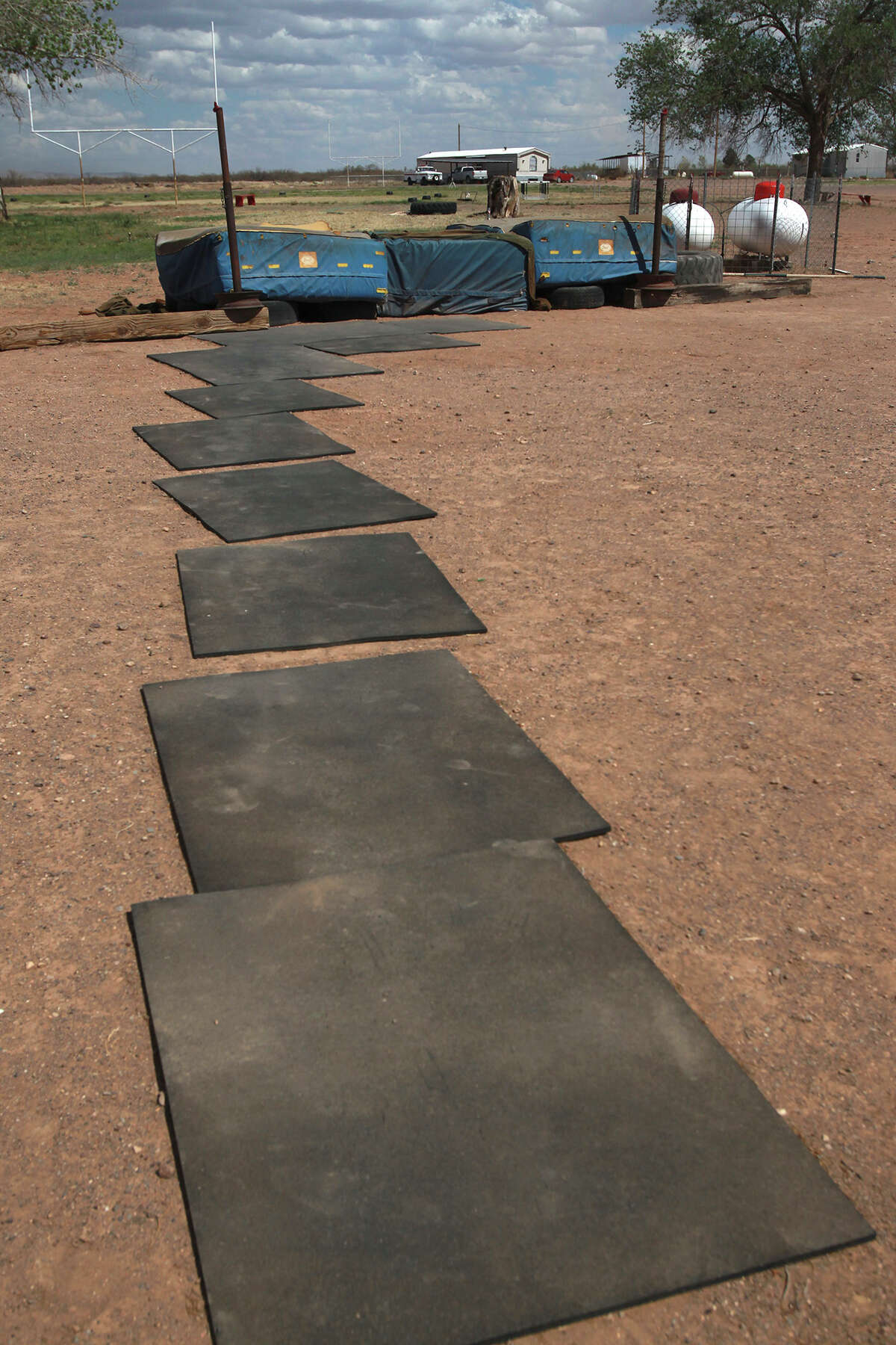 This is the dilapidated high jump pit used by students in the Valentine Independent School district in Valentine, Texas. Valentine, Texas is located in west Texas in Jeff Davis County. Student Latham Garnsey has used the pit with success. Students use the black mats to approach the pit so they don't slip in the gravel.