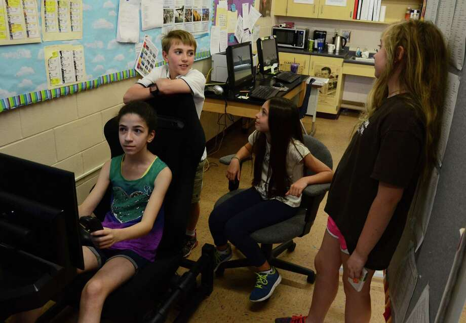 From left to right, fifth-graders Paulina Poteet, Henry Benton, Katherine Morrocu and Hanah Swimm around the flight team's flight simulator at Saxe Middle School, in New Canaan, Conn., Monday, May 12, 2014. Photo: Nelson Oliveira / New Canaan News