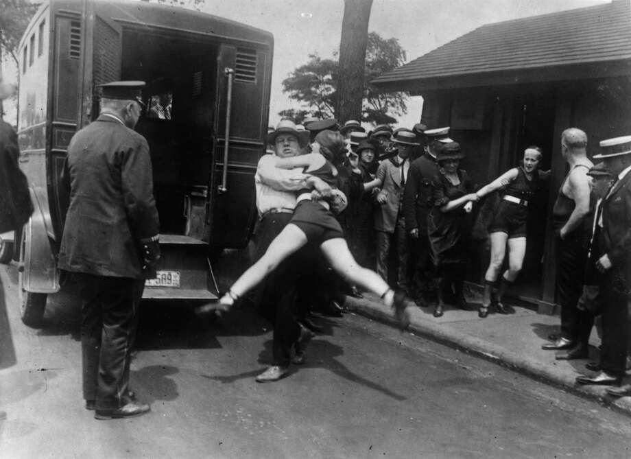 A woman in Chicago being arrested for wearing a one-piece bathing suit without the required leg coverings, July 1922. Photo: Topical Press Agency, Getty Images