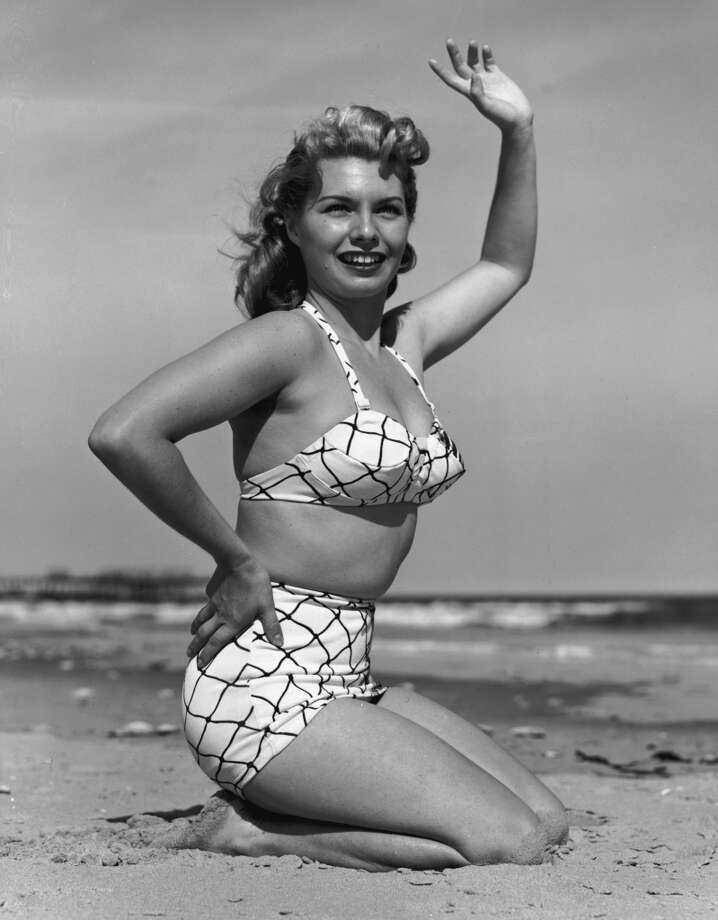 A blonde woman wearing a two-piece bathing suit, kneeling in the sand, smiles and waves on a beach, circa 1945. Photo: Lambert, Getty Images