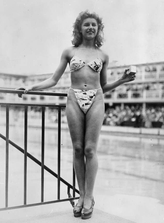 "The new ""bikini"" bathing suit (in a newsprint-patterned fabric because the  the style statement would show up in all the papers), caused a sensation at a beauty contest at the Molitor swimming pool in Paris, July 1946.Designer Louis Reard was unable to find a ""respectable"" model for his costume and the job of displaying it went to 19-year-old Micheline Bernardini, a nude dancer from the Casino de Paris. Here she is seen holding a small box into which the entire costume can be packed. Celebrated as the first bikini, Reard's design came a few months after a similar two-piece design was produced by French designer Jacques Heim. Photo: Keystone, Getty Images"