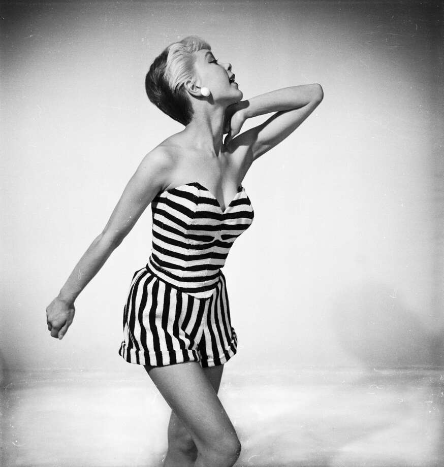 A woman with two-tone color hair models a black and white striped strapless swimsuit on June  1, 1954. Photo: Chaloner Woods, Getty Images