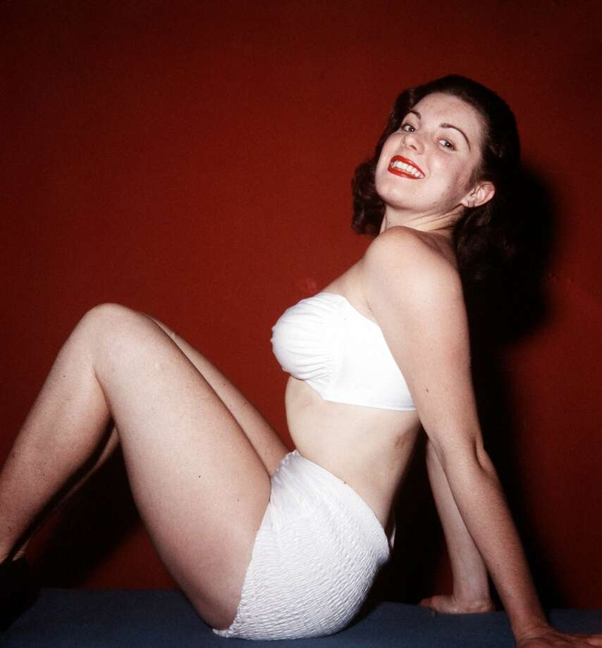A portrait of a young woman wearing a fashionable white two piece swimsuit whilst sitting on the floor smiling at camera, circa 1960s. Photo: Popperfoto, Popperfoto/Getty Images