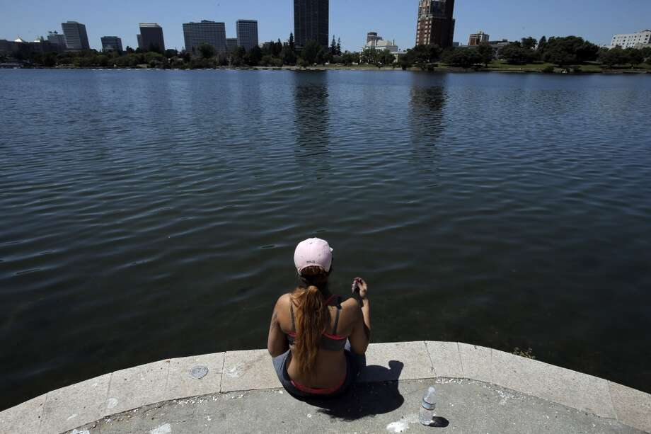 Janay Freeman of Oakland sits by the edge of the water at Lake Merritt on Tuesday, May 14, 2014, in Oakland, Calif. Temperatures soared into the 90s across the Bay Area for the second consecutive day on and were expected to remain high through the end of the week. Photo: Carlos Avila Gonzalez, The Chronicle