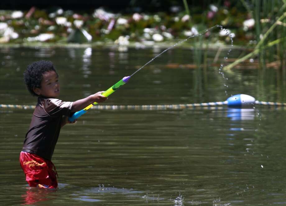 Dyson Kobayashi sprays a stream of water towards friends at Lake Temescal in Oakland, Calif. on Tuesday, May 13, 2014. Rising temperatures are forecast to hit triple digits in some areas of the Bay Area on Wednesday. Photo: Paul Chinn, The Chronicle