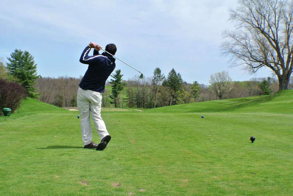 Scott Battiste, the golf professional for Normanside Country Club, drives a ball on the famed 13th green. (Deanna Fox)