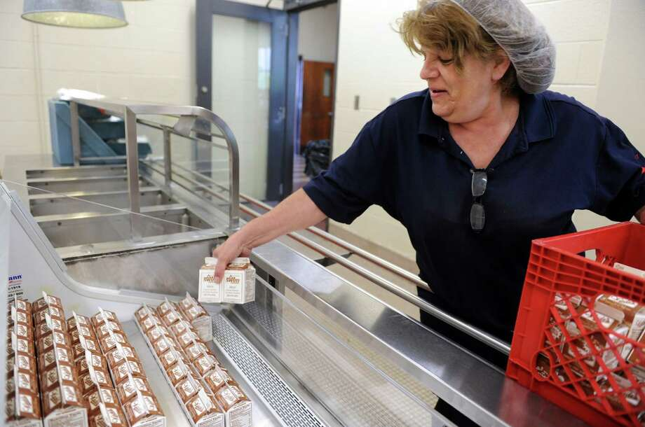 Marie Nickle, cafeteria manager at Harding High School, stocks a case with chocolate milk Wednesday, May 14, 2014, at the school in Bridgeport, Conn. Bill 5566 contains a section that limits what beverages can be sold in schools, including chocolate milk that has added sodium. Photo: Autumn Driscoll / Connecticut Post