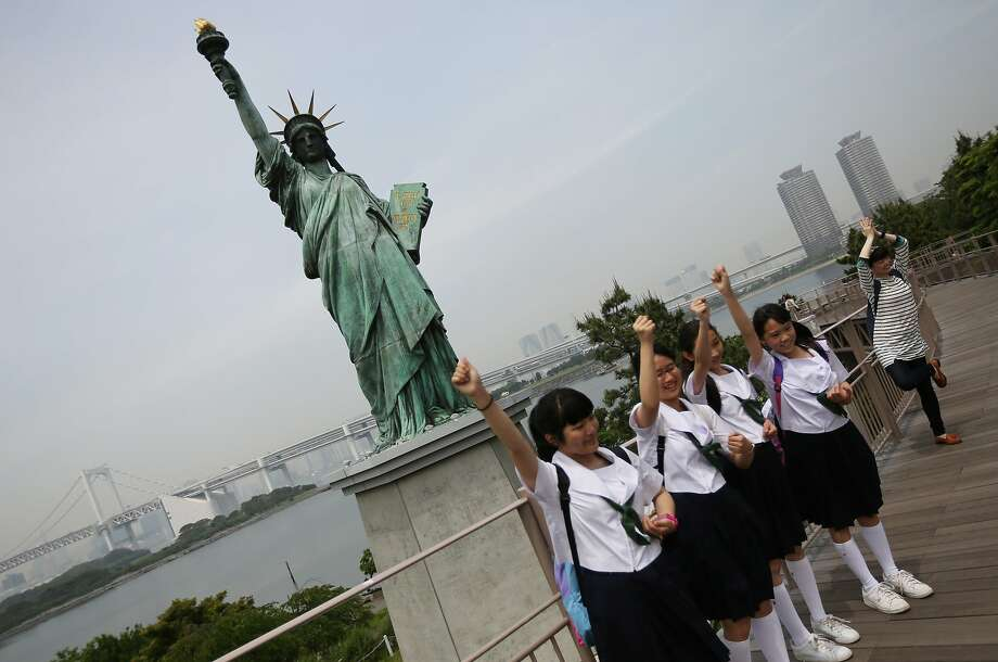 Raise your arm if you're sure: Students on a school excursion pose in front of a replica of the Statue of Liberty at Odaiba in Tokyo. Photo: Eugene Hoshiko, Associated Press