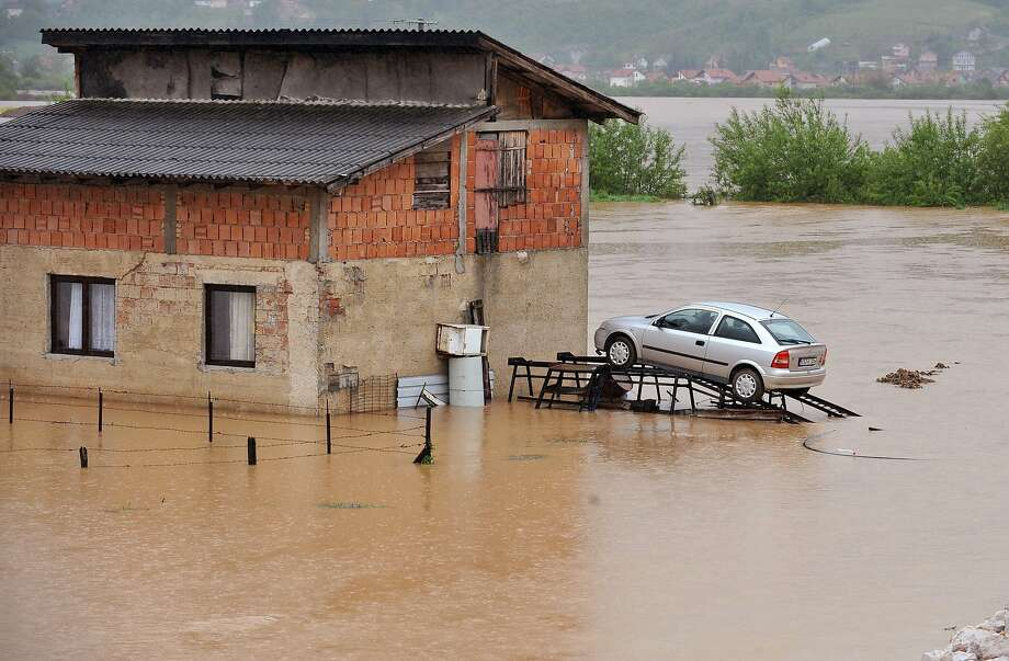 Safe for now: A car on a ramp escapes the rising Bosna River in Sarajevo's Western suburb 