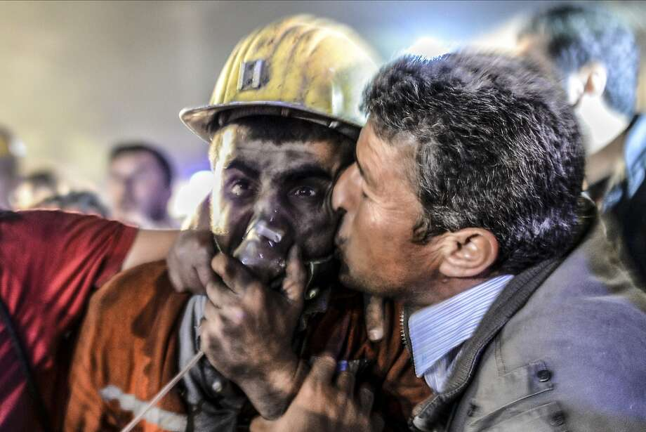 A man kisses his son as the rescued miner breathes oxygen following an explosion and fire 