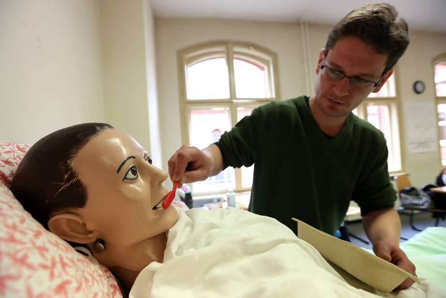 Open wide ... wider: Student Frank Schreiber brushes the teeth of a mannequin named Frau Schmidt during an elderly care training program at the Edith Stein Catholic vocational training center in Berlin. The supply of caregivers for the elderly in Germany has not met the demand. Photo: Adam Berry, Getty Images