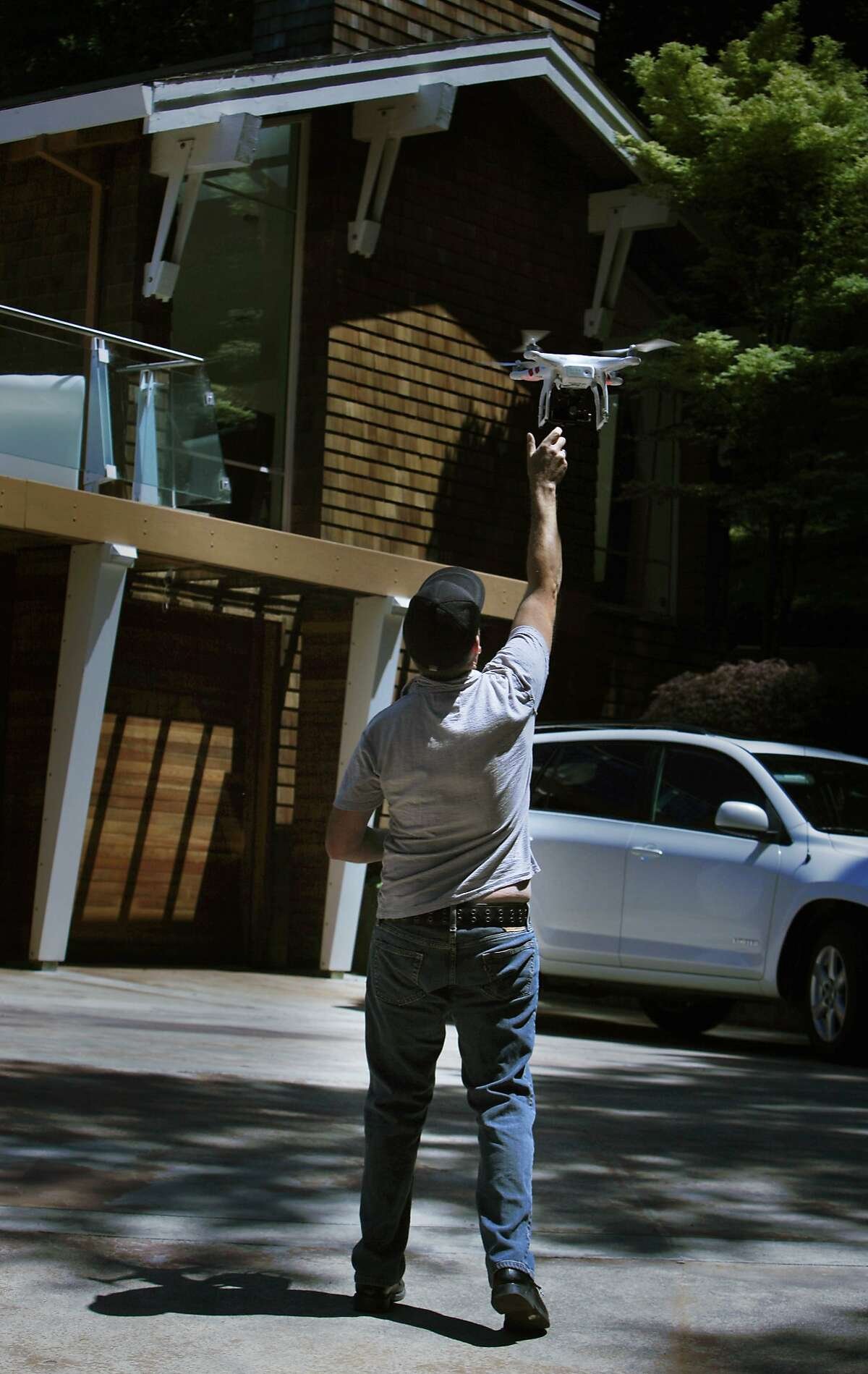Videographer Doug Canning catches a remote-controlled quadcopter while setting it up to take an aerial video of a home in Corte Madera on Tuesday, May 13, 2014 in Corte Madera, Calif.