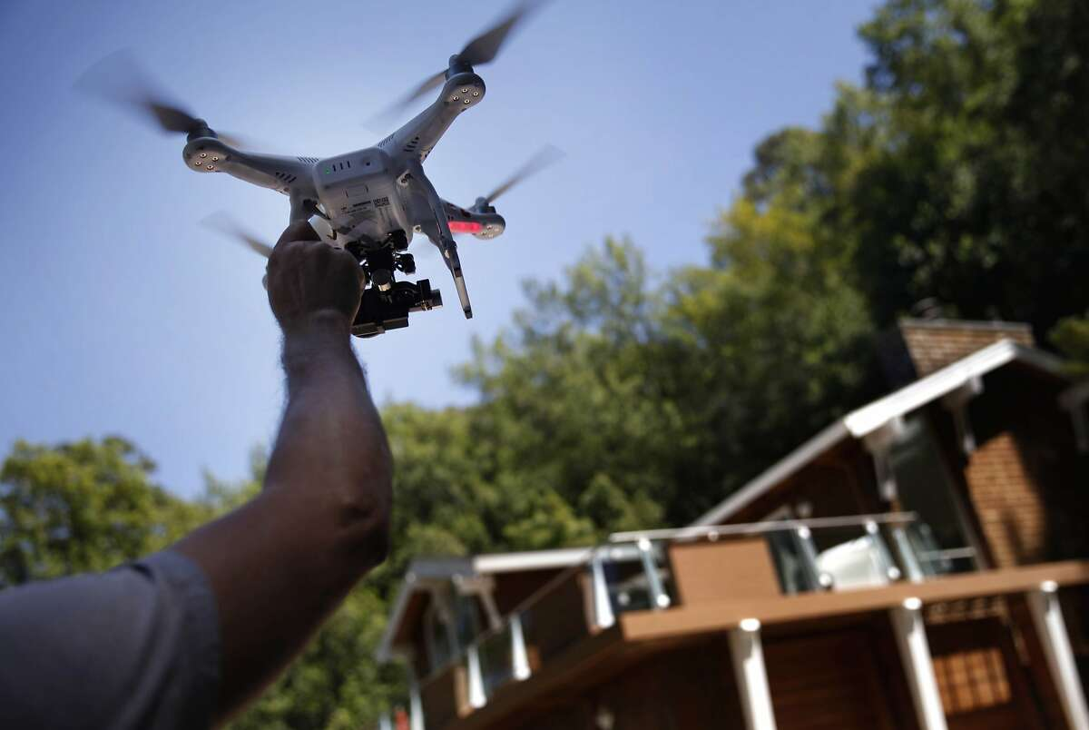 Videographer Doug Canning catches a remote-controlled quadcopter after using it to take an aerial video of a home in Corte Madera on Tuesday, May 13, 2014 in Corte Madera, Calif.