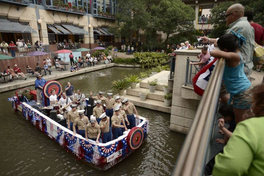 U.S. Marines wave to spectators during last year's America's Armed Forces River Parade. Photo: Express-News, File