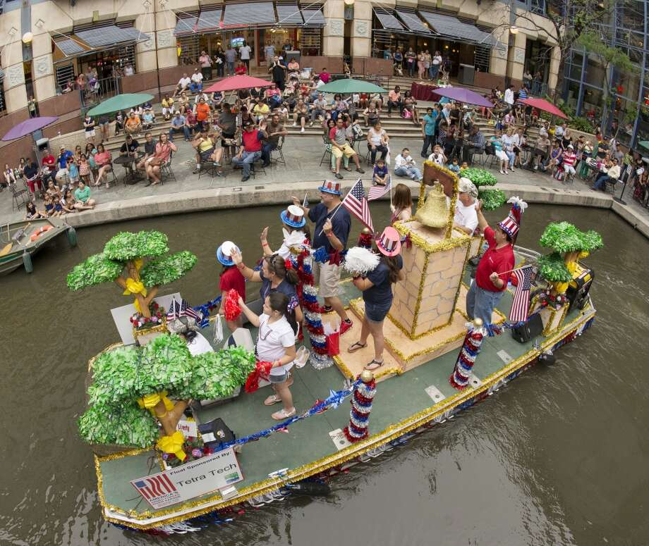Participants on a float wave to spectators in the Rivercenter mall lagoon during last year's America's Armed Forces River Parade. Photo: Express-News, File