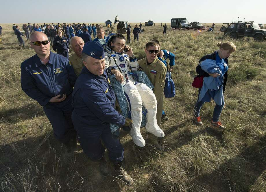 ZHEZKAZGAN,KAZAKHSTAN - MAY 14:   Expedition 39 Commander Koichi Wakata of the Japan Aerospace Exploration Agency (JAXA) is carried in a chair to a medical tent just minutes after he and Soyuz Commander Mikhail Tyurin of Roscosmos, and Flight Engineer Rick Mastracchio of NASA, landed in their Soyuz TMA-11M spacecraft on May 14, 2014 near the town of Zhezkazgan, Kazakhstan. Wakata, Tyurin and Mastracchio returned to Earth after more than six months onboard the International Space Station where they served as members of the Expedition 38 and 39 crews. (Photo by Bill Ingalls/NASA via Getty Images) *** BESTPIX *** Photo: Bill Ingalls/NASA, NASA Via Getty Images