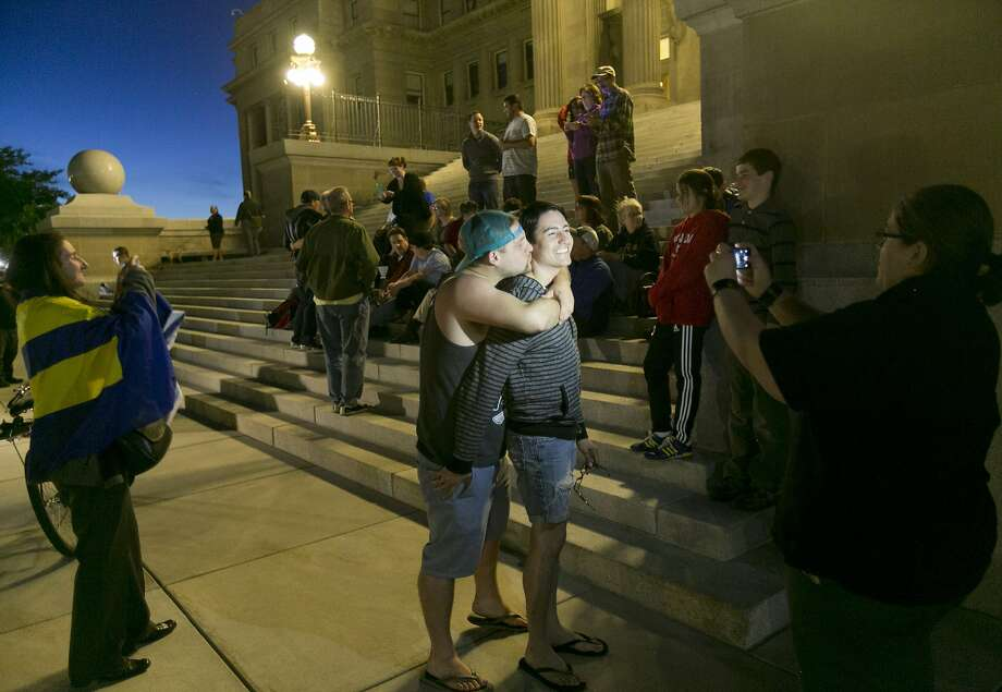 Mike Chase, center left, kisses his partner Matthew Montoya on the steps of the Idaho Statehouse during a rally in support of same sex marriage in Boise on Tuesday night May 13, 2014. U.S. Magistrate Judge Candy Dale ruled earlier in the day that Idaho's ban on gay marriage is unconstitutional. (AP Photo/The Idaho Statesman, Kyle Green) Photo: Kyle Green, Associated Press