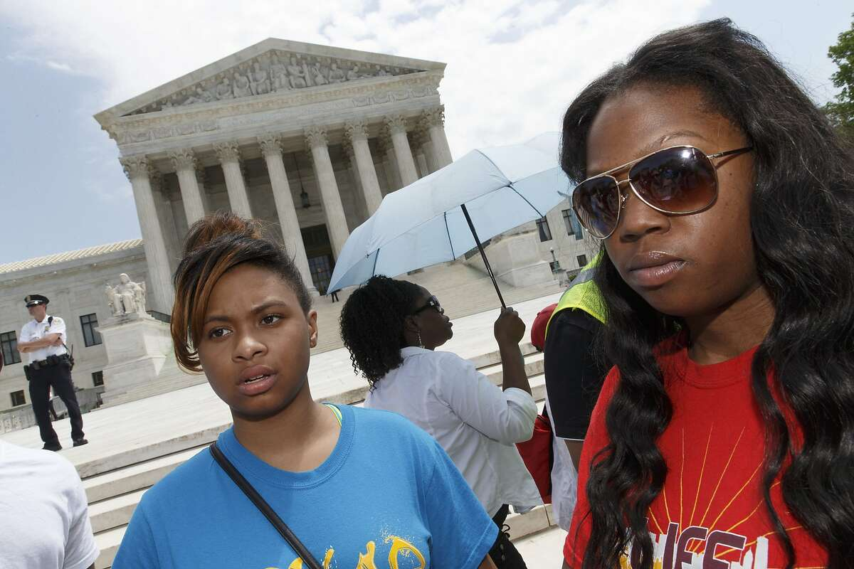 Diamond McCullough, 17, left, and Aquila Griffin, 18, right, talk about their high school education experience in Chicago as students, parents and educators rally at the Supreme Court in Washington, Tuesday, May 13, 2014, on the 60th anniversary Brown v. Board of Education, the decision that struck down the