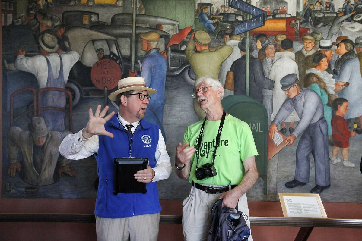 San Francisco Walking Tour guide Rory O'Connor, left, talks with Don Cropp about the murals during the reopening of Coit Tower May 14, 2014 in San Francisco, Calif. The tower is open again to the public after being closed for a number of months for conservation and restoration work.