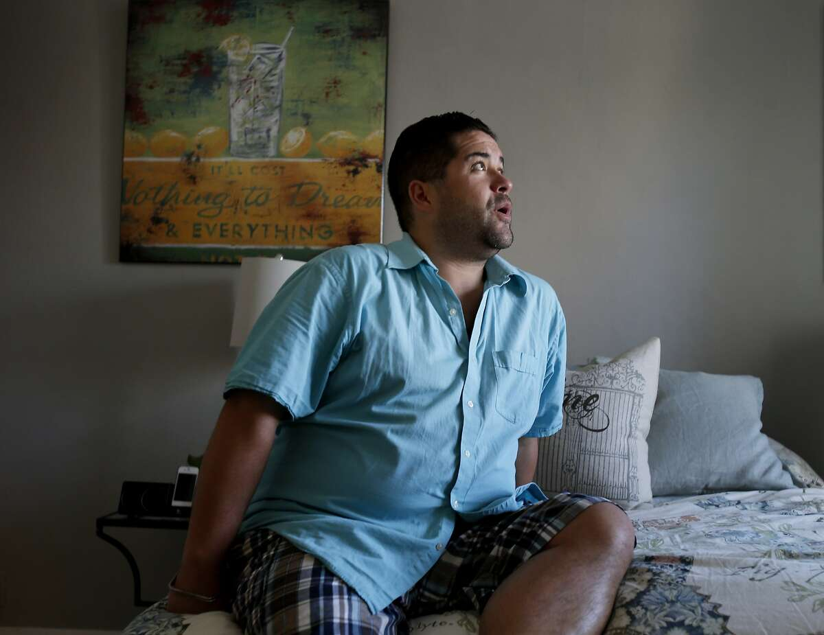Brent Sanchez has relied on friends for medical care recently. He sits on his bed in his Tenderloin apartment Wednesday May 14, 2014. Brent Sanchez is a waiter and bartender who works 40 hours a week and still can't afford health insurance in San Francisco, Calif.