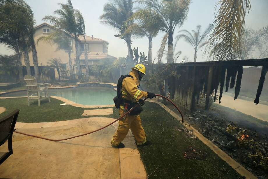 A firefighter puts water on a house fence during a wildfire in Carlsbad (San Diego County). Photo: Uncredited, Associated Press