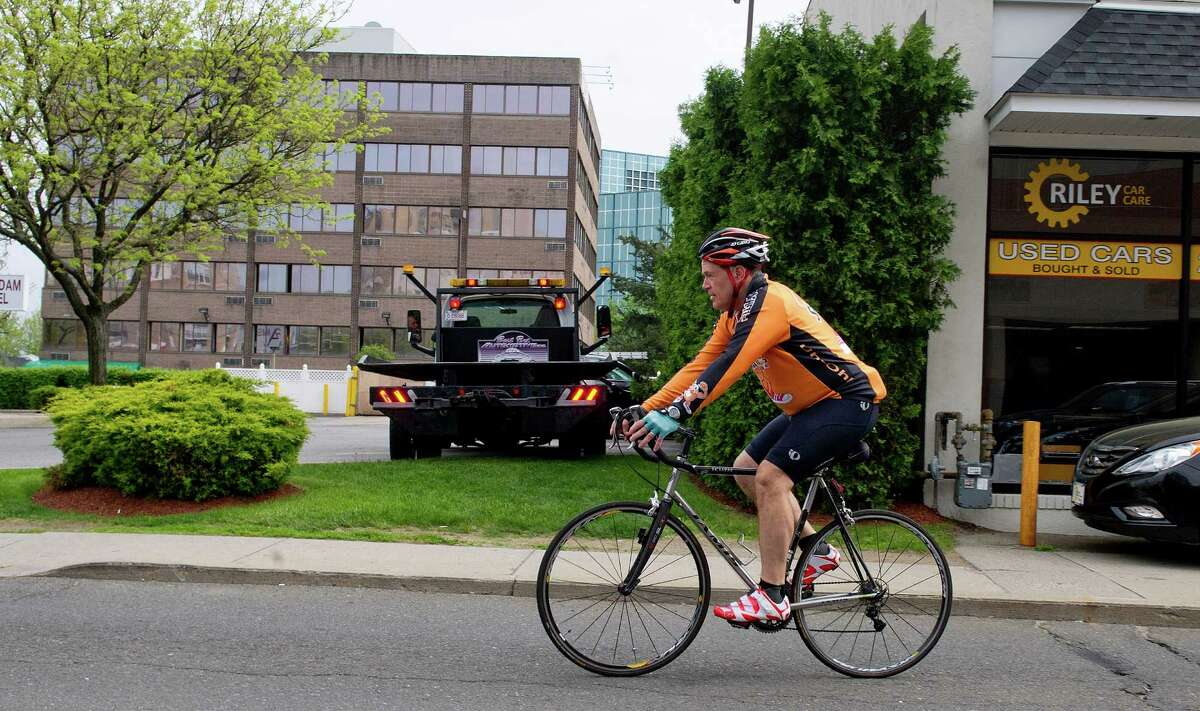 Doug Fried rides his bike home to Southport from his Stamford office after work on Wednesday, May 14, 2014.