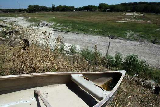 A canoe hangs on a limestone cliff over an area between Pipe Creek, Texas, and Medina Lake where the Medina River used to flow. The state's drought has affected real estate in the river and lakefront areas. Photo: SAN ANTONIO EXPRESS-NEWS