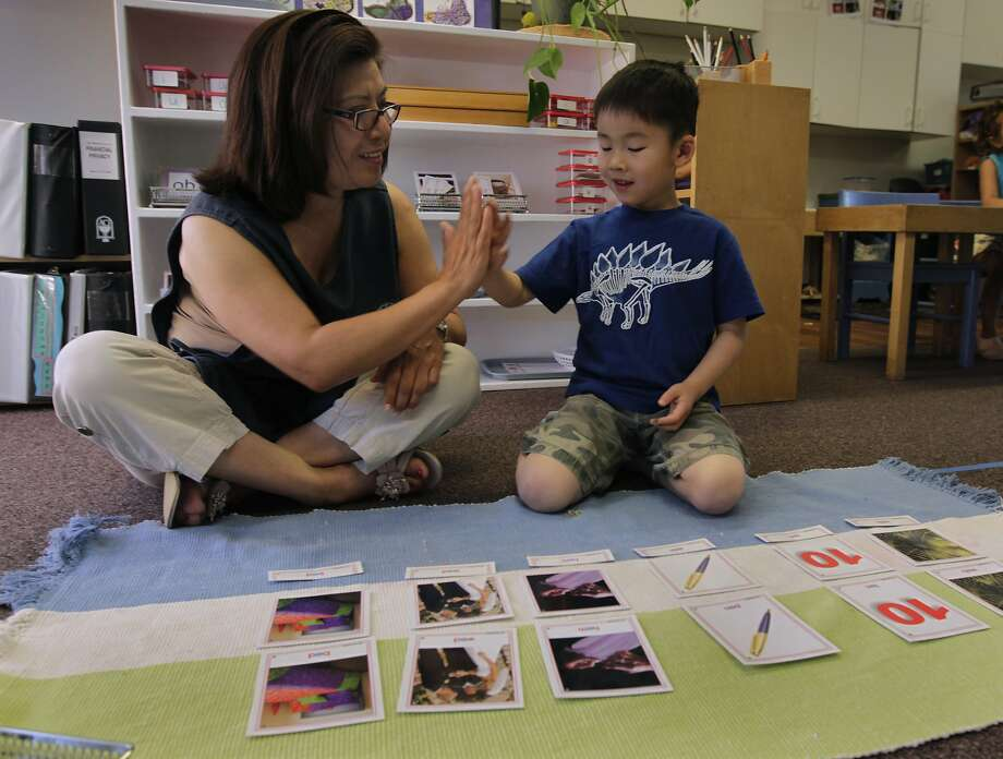 Teacher Sonia Castro high-fives student Alfred Chen during a lesson at the Montessori School at Five Canyons in Castro Valley. The school was not included in the UC Berkeley study and has taken steps to make the environment as safe as possible for kids. Photo: Paul Chinn, The Chronicle