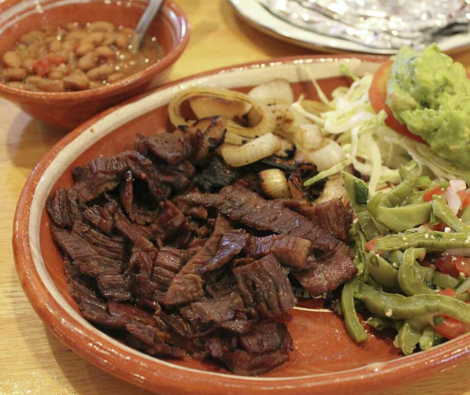 El Machito offers a selection of grilled meats, including cecina, or thinly sliced beef that's partially dried with salt and olive oil. Served here with frijoles charros and ensalada de nopalitos. Photo: Jennifer McInnis, San Antonio Express-News