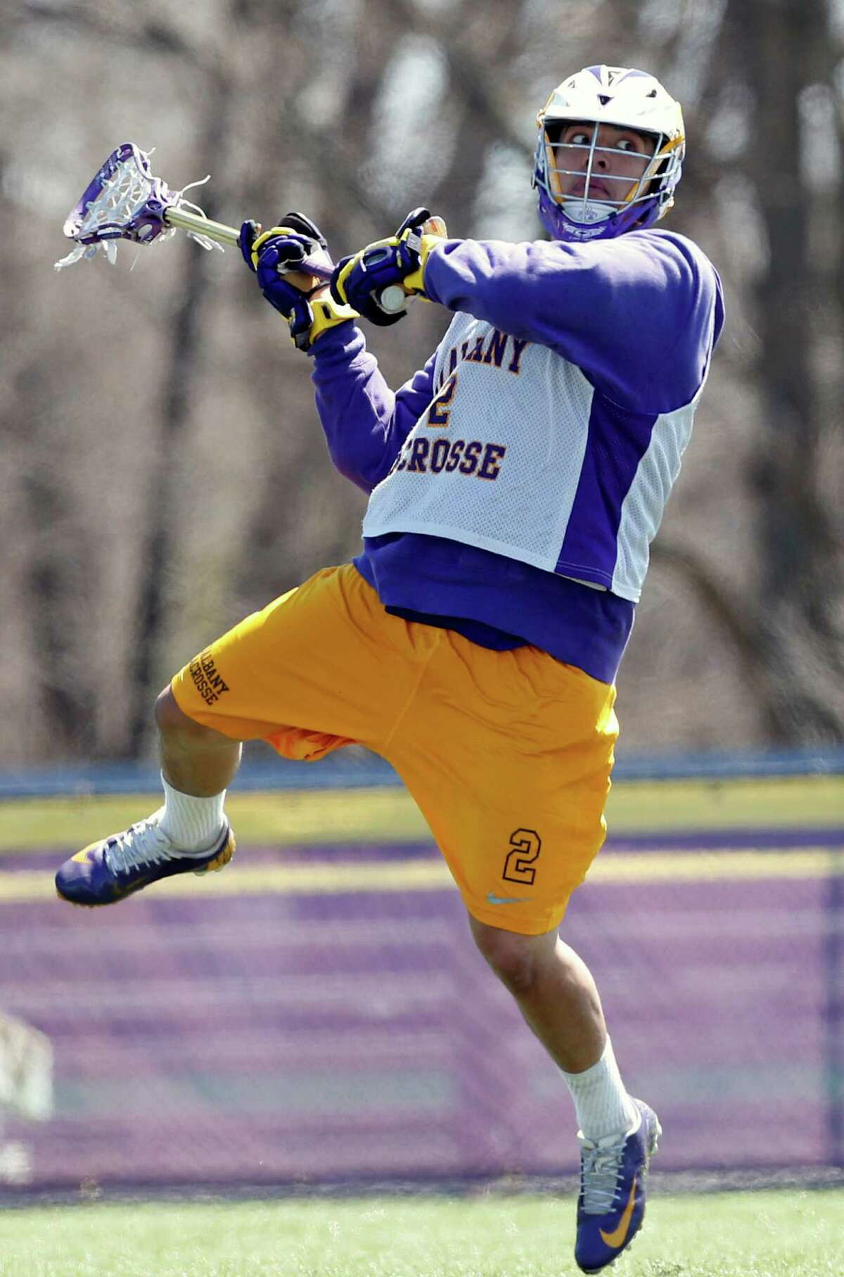 In this photo taken on Monday, April 28, 2014, University at Albany lacrosse player Miles Thompson (2) practices in Albany, N.Y. A trio of Native American players, Miles, younger brother Lyle, and cousin Ty, have transformed Albany into an offensive juggernaut in Division I men's lacrosse. (AP Photo/Mike Groll) ORG XMIT: NYMG203