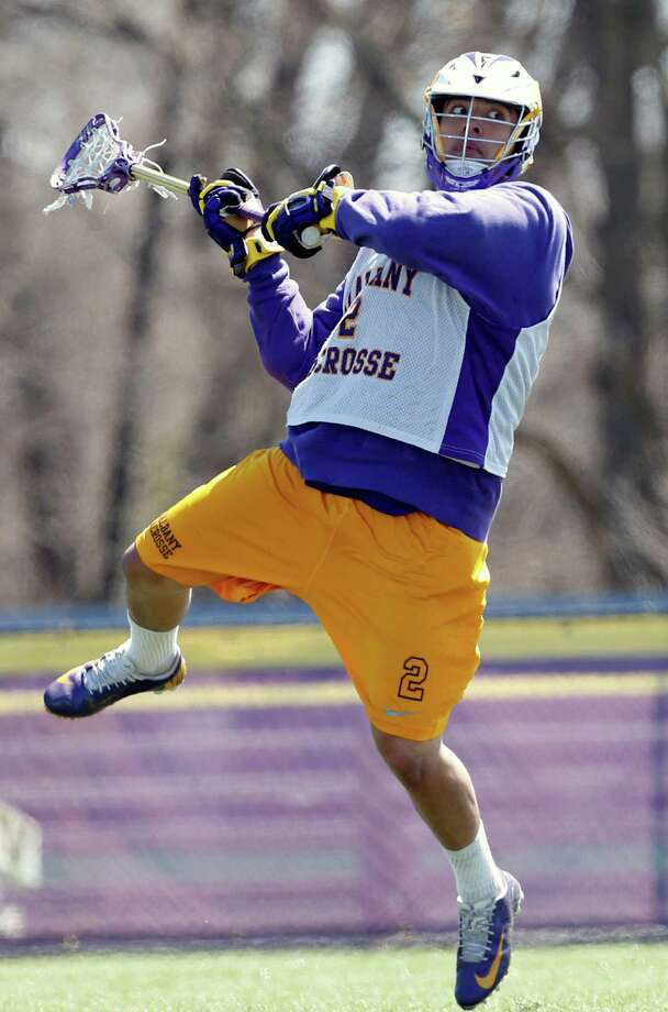 In this photo taken on Monday, April 28, 2014, University at Albany lacrosse player Miles Thompson (2) practices in Albany, N.Y.  A trio of Native American players, Miles, younger brother Lyle, and cousin Ty, have transformed Albany into an offensive juggernaut in Division I men's lacrosse.  (AP Photo/Mike Groll) ORG XMIT: NYMG203 Photo: Mike Groll / AP