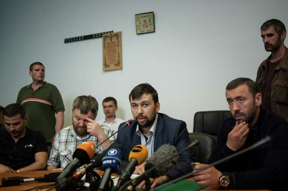 "Denis Pushilin, center, a leader of the insurgency that has declared an independent ""people's republic"" in the Donetsk region, speaks at a news conference in eastern Ukraine city of Donetsk on Wednesday May 14, 2014. Pushilin said his faction wasn't invited to a government-organized roundtable talks in Kiev. (AP Photo/Evgeniy Maloletka) Photo: Evgeniy Maloletka, STR / AP"