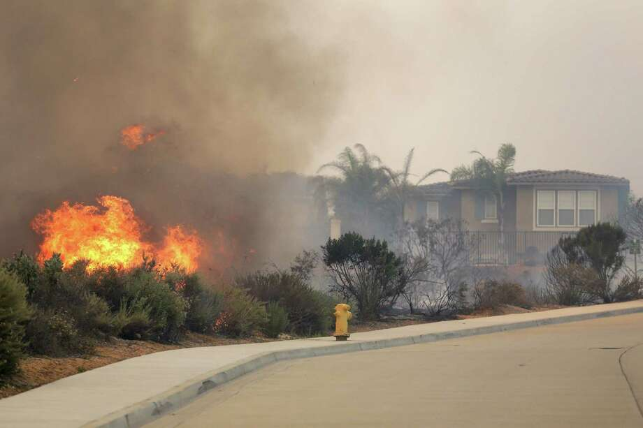 A wildfire climbs a canyon toward homes on Wednesday in Carlsbad, Calif. More wildfires broke out Wednesday in San Diego County - threatening homes in Carlsbad and forcing the evacuations. Photo: STF / AP
