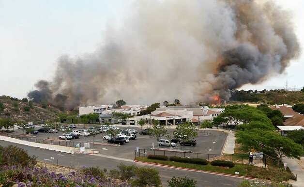 A wildfire burns toward Aviara Oaks Middle School on May 14, 2014, in Carlsbad, Calif., the Associated Press reports.  Wind-driven flames threatened homes in the coastal city of Carlsbad, where officials sent mandatory evacuation notices to more than 11,000 homes and businesses. Photo: STF / AP