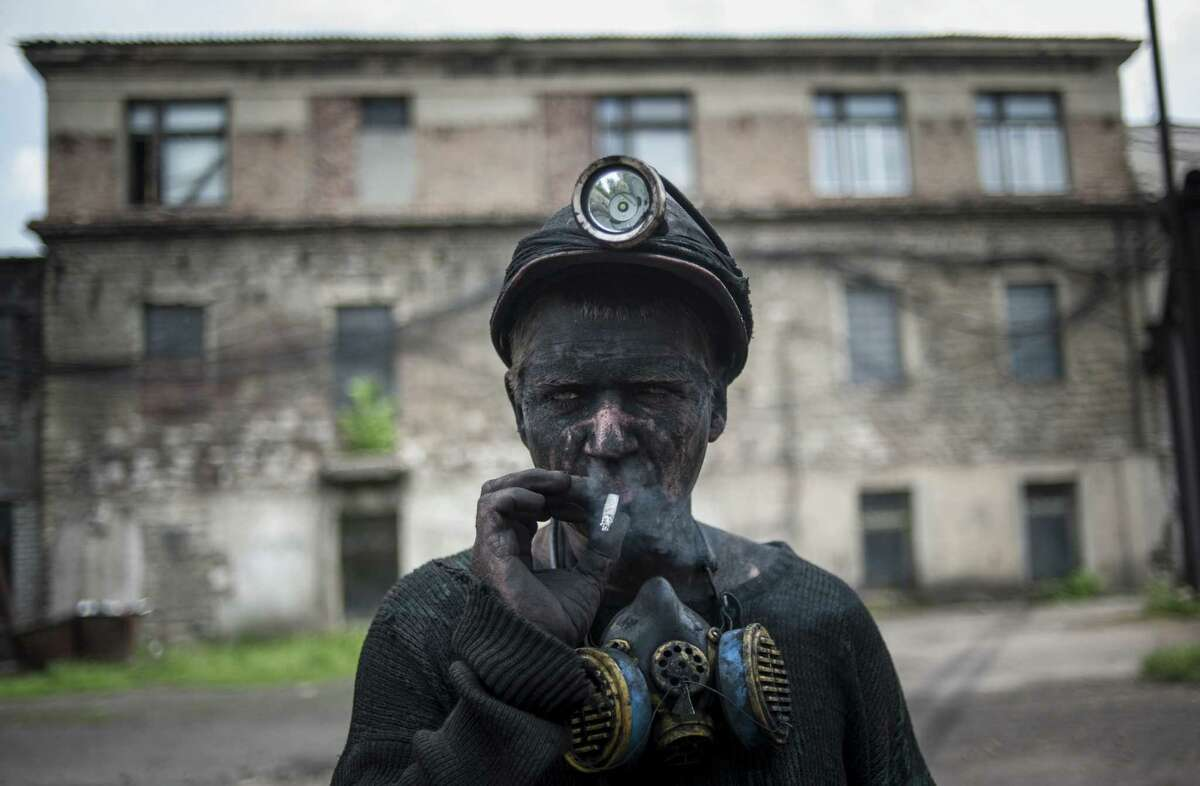 A Ukrainian miner smokes at an eastern Ukraine mine. Without the east's pro-Russian insurgents, Ukrainian officials began talks on decentralizing power as part of a European-backed peace plan.
