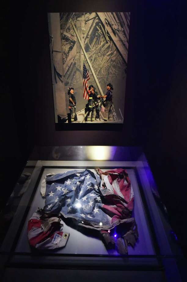 An American flag found at the World Trade Center site (below) and a photograph of a flag raising at the site by Thomas E. Franklin/The Record (Bergen County, New Jersey) (top), seen during a press preview of the National September 11 Memorial Museum at the World Trade Center site May 14, 2014 in New York. Photo: STAN HONDA, AFP/Getty Images / AFP