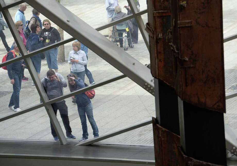 "People peer in at the World Trade Center ""tridents"" (R), two steel columns that formed part of the building's structural support, seen in the National September 11 Memorial Museum at the World Trade Center site May 14, 2014 in New York. Photo: STAN HONDA, AFP/Getty Images / AFP"