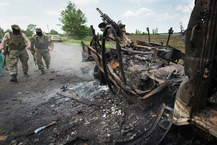Two armed pro-Russians walk towards a seized military track with a mortar atop that was set alight during fighting between pro-Russian militants and government troops at Oktyabrskoye village, about 20 km (12 miles) from Kramatorsk, eastern Ukraine, Wednesday, May 14, 2014. At list six servicemen were ambushed and killed and eight others wounded Tuesday afternoon outside the town of Kramatorsk, Ukrainian defense ministry said. (AP Photo/Alexander Zemlianichenko) ORG XMIT: XAZ124 Photo: Alexander Zemlianichenko / AP