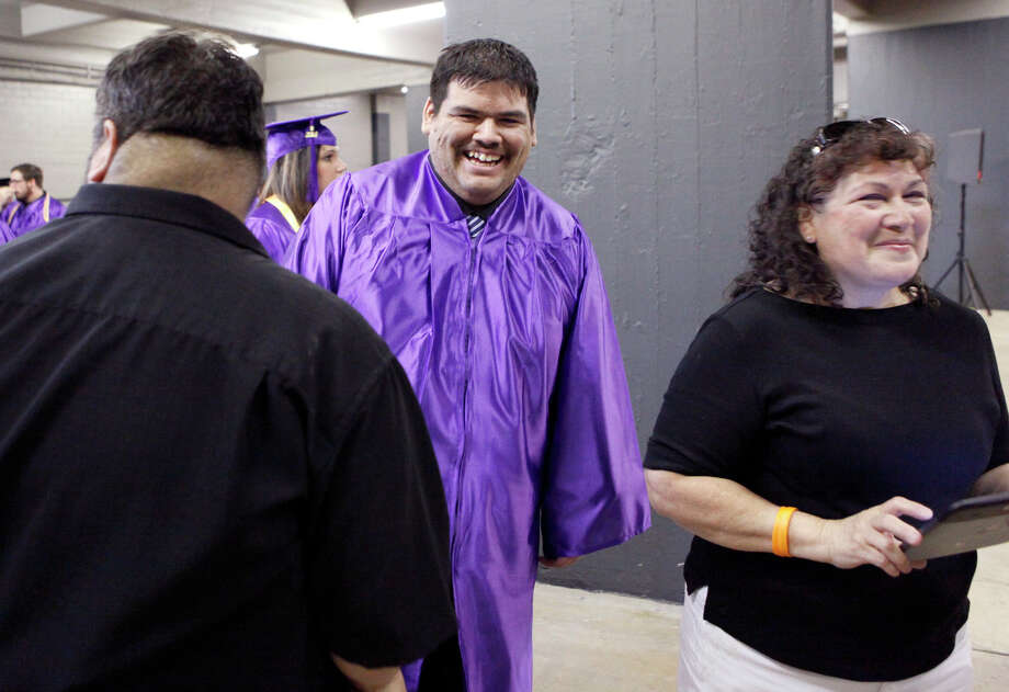 Dylan Barrera talks with his parents, Ruby and Dean,  before the graduating from Northwest Vista College. Photo: Cynthia Esparza, For The San Antonio Express-News / SAN ANTONIO EXPRESS-NEWS