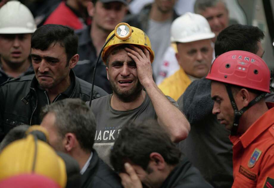 A miner cries as rescue workers carry the dead body of a miner from the mine in Soma, western Turkey, Wednesday, May 14, 2014. An explosion and fire at the coal mine killed at least 232 workers, authorities said, in one of the worst mining disasters in Turkish history. Turkey's Energy Minister Taner Yildiz said 787 people were inside the coal mine at the time of the accident. (AP Photo/Emrah Gurel) ORG XMIT: ANK165 Photo: Emrah Gurel / AP