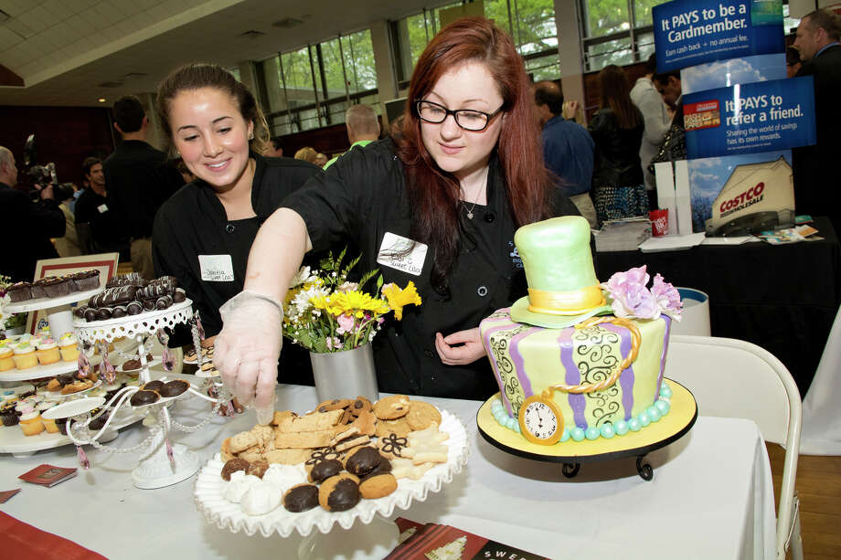 Jessi Vitti, pastry chef at Sweet Lisa's Exquisite Cakes, arranges treats on a stand, as fellow pastry chef Daniela Catenacci, at left, looks on during the Business & Culinary Showcase at Eastern Greenwich Civic Center in Old Greenwich, Connecticut on Wednesday, May 14, 2014. Photo: Amy Mortensen / Connecticut Post Freelance