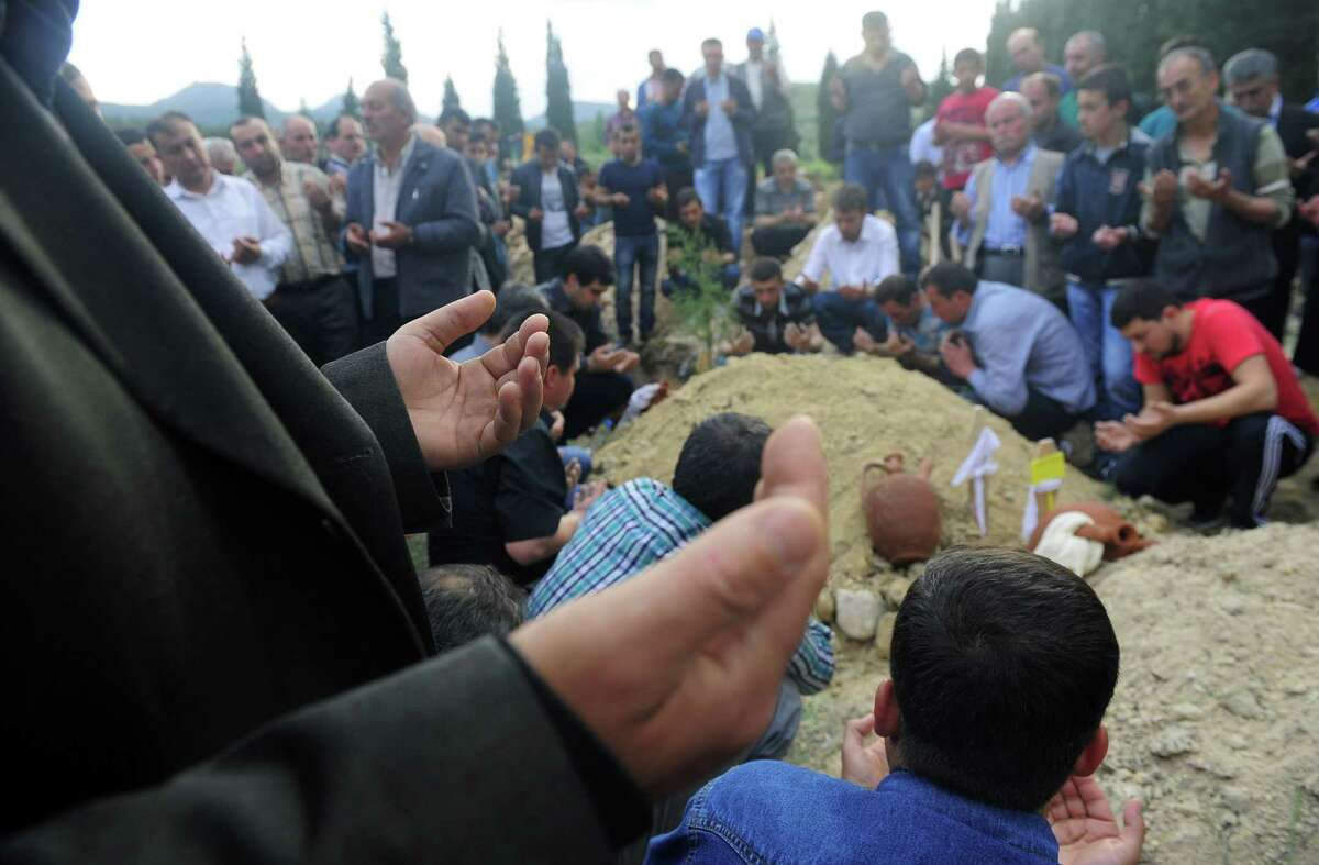 Mourners attend a mine accident victim's burial in Soma, Turkey. Nearly 450 miners were rescued, the mining company said, but the fate of an unknown number of others remained unclear as bodies are still being brought to the surface.