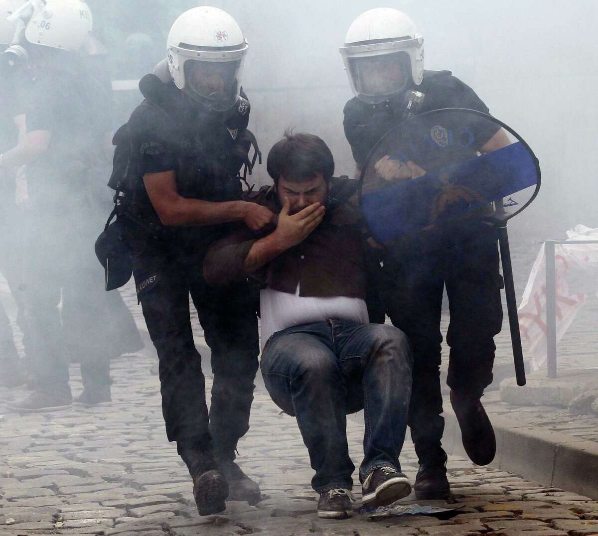 Turkish police arrest a protester in Ankara, where hundreds gathered after more than 270 people were killed in an explosion at a mine.