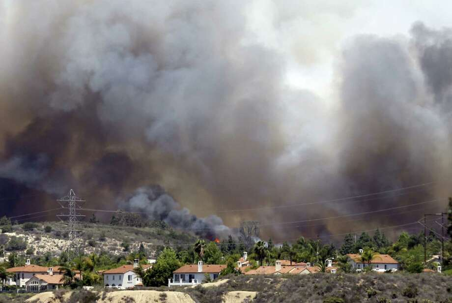 Wildfire climbs a canyon toward homes in Carlsbad, California. More wildfires broke out Wednesday in San Diego County as the area endured a heat wave. Photo: Associated Press / AP