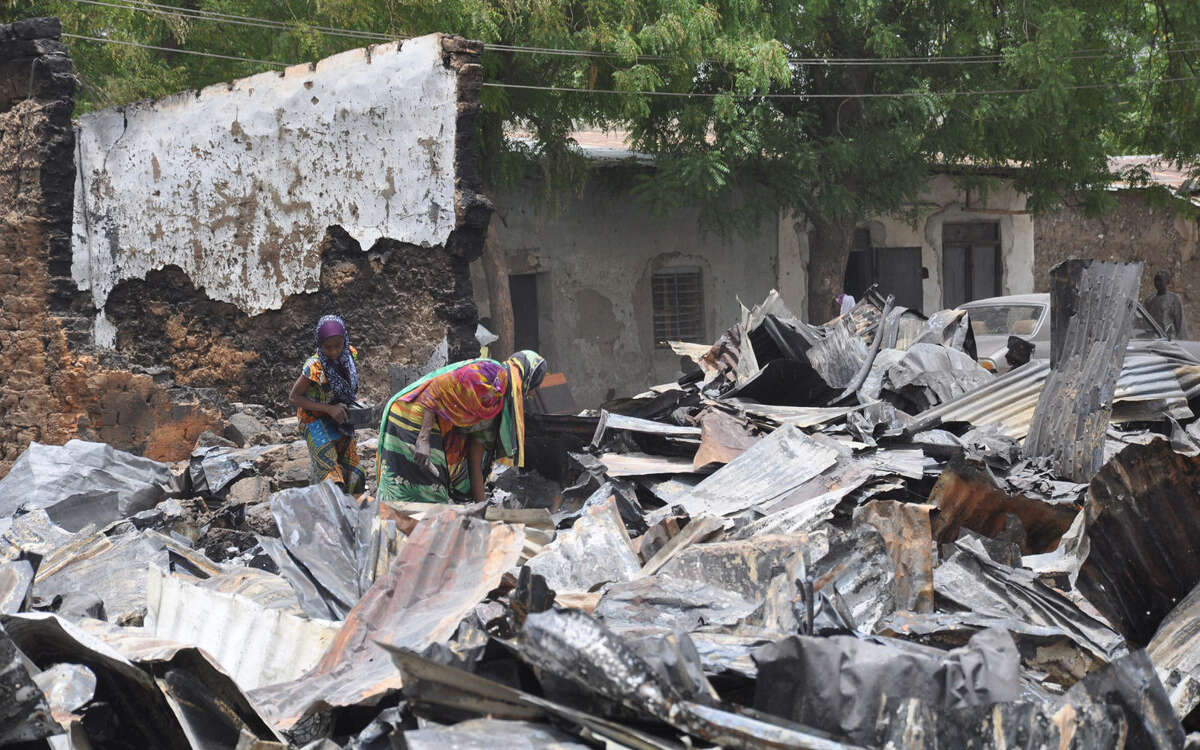 Women search for valuables at a burnt-out house following an attack by Islamic militants in Gambaru, Nigeria.