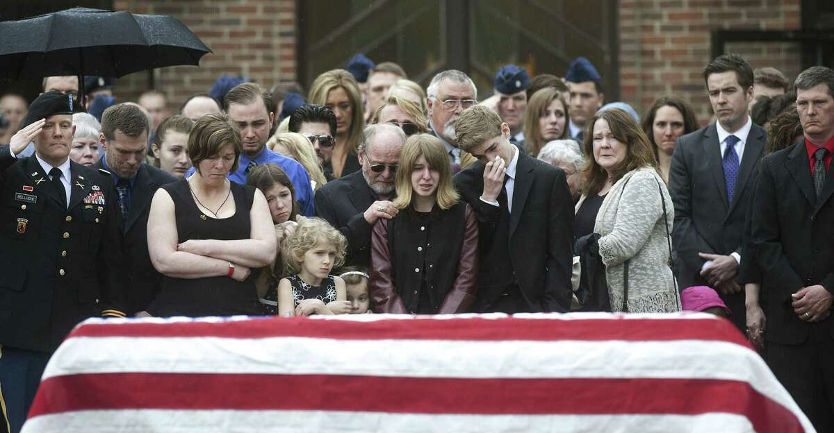 Family, friends and members of the military gather beside Kryn Miner's casket after his May 2 funeral outside St. Lawrence Church in Essex, Vt.