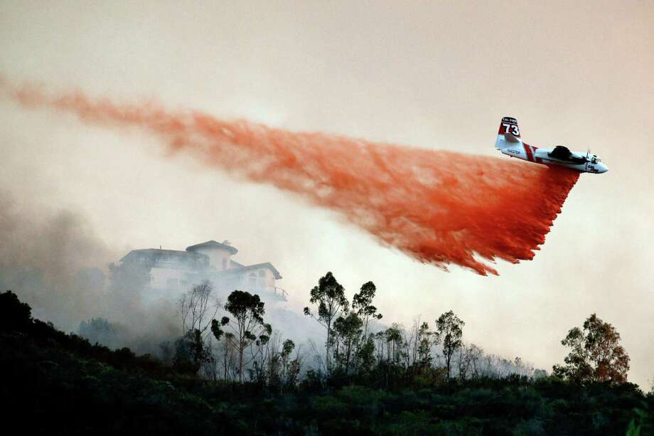 A plane drops fire retardant over a hot spot on Wednesday, May 14, 2014, in San Marcos, Calif. Wednesday, May 14, 2014, in San Marcos, Calif. Flames engulfed suburban homes and shot up along canyon ridges in one of the worst of several blazes that broke out Wednesday in Southern California during a second day of a sweltering heat wave, taxing fire crews who fear the scattered fires mark only the beginning of a long wildfire season. Photo: AP / AP